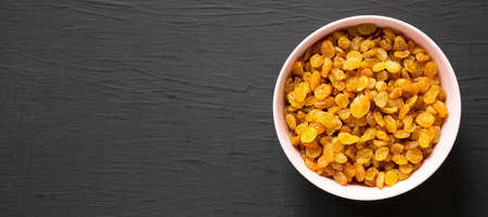 Golden Raisins in a Pink Bowl on a black surface, top view. Flat lay, overhead, from above. Copy space. Standard-Bild