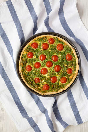 Homemade Spinach Quiche in a baking dish on a white wooden surface, top view. Flat lay, overhead, from above.