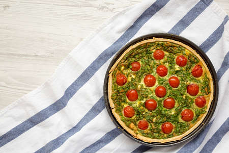 Homemade Spinach Quiche in a baking dish on a white wooden background, top view. Flat lay, overhead, from above. Copy space.
