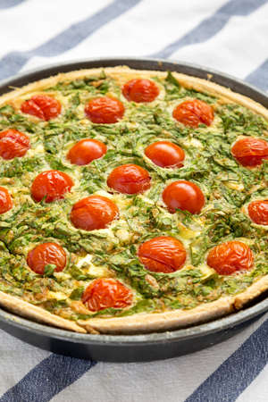 Homemade Spinach Quiche in a baking dish, low angle view. Close-up.