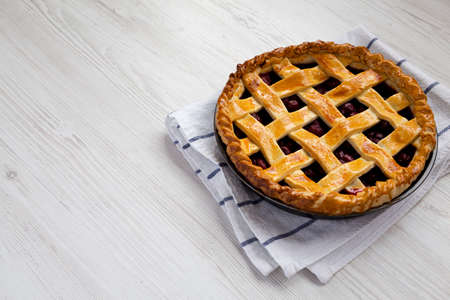 Yummy Homemade Cherry Pie on a white wooden table, side view. Copy space.