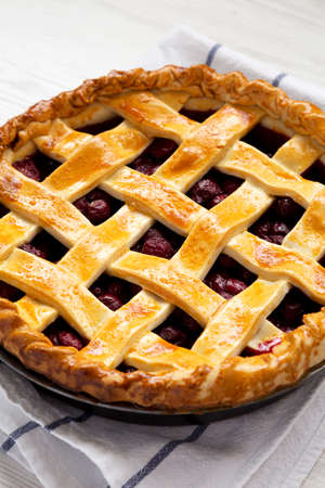 Yummy Homemade Cherry Pie on a white wooden background, low angle view. Close-up. 写真素材