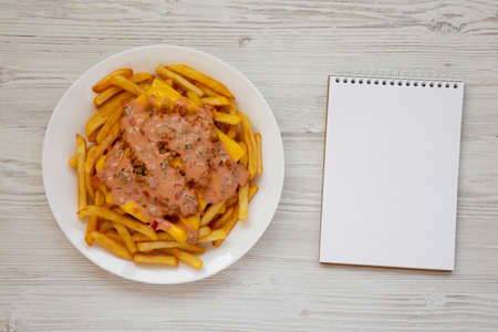 Homemade Animal Style French Fries on a white plate, blank notepad on a white wooden surface, overhead view. Flat lay, top view, from above. Space for text.
