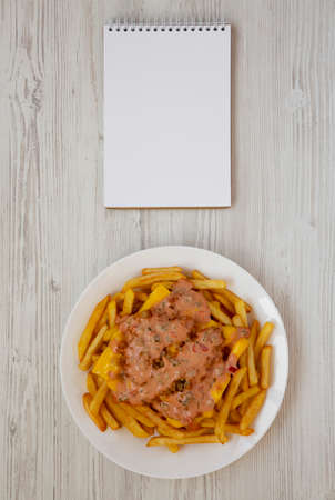Homemade Animal Style French Fries on a white plate, blank notepad on a white wooden background, top view. Flat lay, overhead, from above. Space for text.