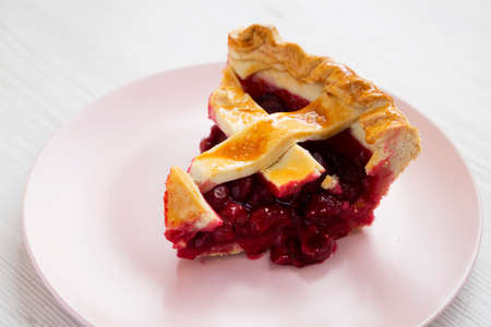 Yummy Homemade Cherry Pie on a pink plate on a white wooden background, low angle view. Close-up.