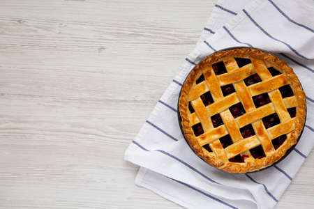 Yummy Homemade Cherry Pie on a white wooden table, top view. Flat lay, overhead, from above. Space for text.