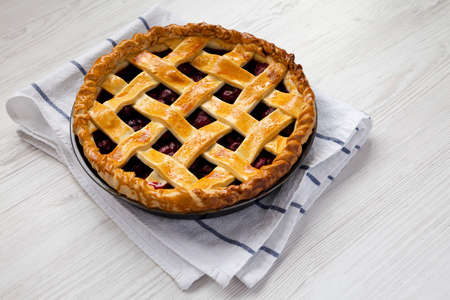 Yummy Homemade Cherry Pie on a white wooden table, side view. Space for text.