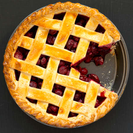Yummy Homemade Cherry Pie on black background, top view. Flat lay, overhead, from above.