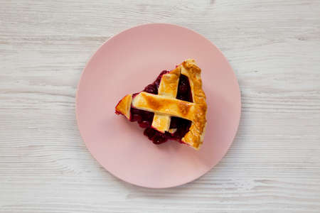 Slice of Yummy Homemade Cherry Pie on a pink plate on a white wooden table, top view. Flat lay, overhead, from above.