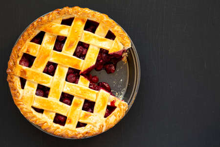 Yummy Homemade Cherry Pie on black background, top view. Flat lay, overhead, from above. Copy space.