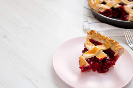 Yummy Homemade Cherry Pie on a pink plate on a white wooden background, low angle view. Space for text.