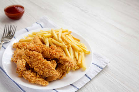 Homemade Crispy Chicken Tenders and French Fries on a white plate, side view. Space for text. Standard-Bild