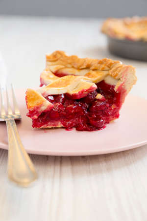 Slice of Yummy Homemade Cherry Pie on a pink plate on a white wooden background, side view. Close-up.
