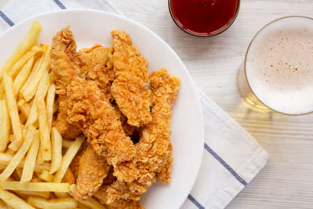 Homemade Crispy Chicken Tenders and French Fries with sauce and glass of cold beer, view from above. Top view, overhead, flat lay.