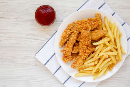 Homemade Crispy Chicken Tenders and French Fries on a white plate, top view. Flat lay, overhead, from above. Copy space.