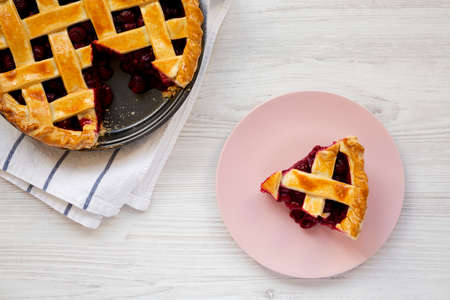 Yummy Homemade Cherry Pie on a pink plate on a white wooden background, top view. Flat lay, overhead, from above.