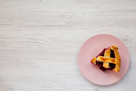 Slice of Yummy Homemade Cherry Pie on a pink plate on a white wooden background, top view. Flat lay, overhead, from above. Copy space.