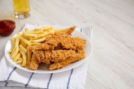 Homemade Crispy Chicken Tenders and French Fries with sauce and glass of cold beer, side view. Copy space.