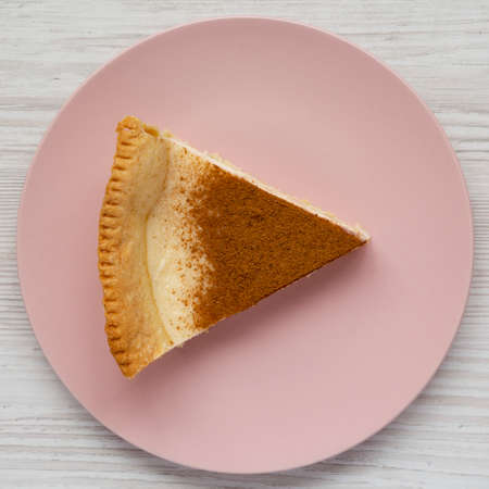 Homemade Sugar Cream Pie on a pink plate on a white wooden background, top view. Flat lay, overhead, from above. 写真素材