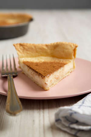 Homemade Sugar Cream Pie on a pink plate on a white wooden background, side view. Close-up.