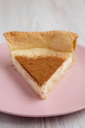 Homemade Sugar Cream Pie on a pink plate on a white wooden background, low angle view. Close-up. 写真素材