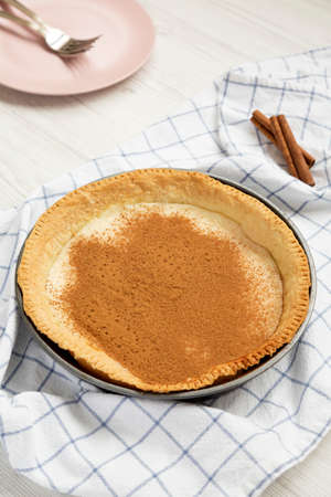 Homemade Sugar Cream Pie in a baking dish on a white wooden background, low angle view.