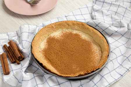 Homemade Sugar Cream Pie in a baking dish on a white wooden surface, low angle view.