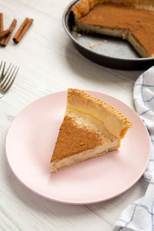 Homemade Sugar Cream Pie on a pink plate on a white wooden surface, low angle view. Close-up.