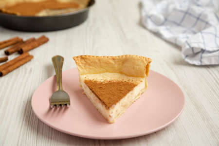 Homemade Sugar Cream Pie on a pink plate on a white wooden table, low angle view.