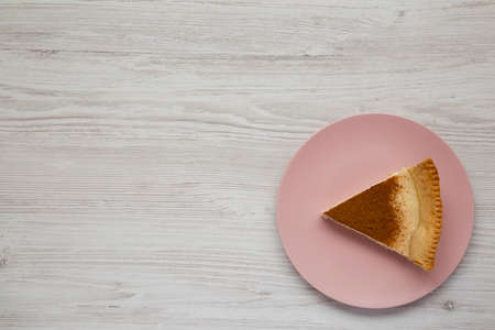 Homemade Sugar Cream Pie on a pink plate on a white wooden background, top view. Flat lay, overhead, from above. Copy space. 写真素材