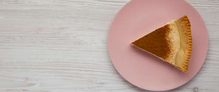 Homemade Sugar Cream Pie on a pink plate on a white wooden surface, top view. Flat lay, overhead, from above. Copy space.