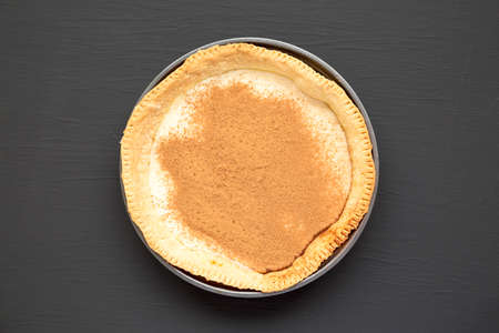 Homemade Sugar Cream Pie in a baking dish on a black background, top view. Overhead, from above, flat lay.
