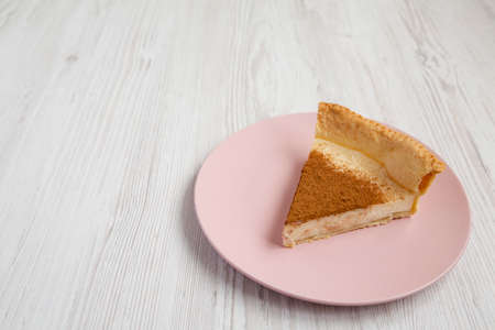 Homemade Sugar Cream Pie on a pink plate on a white wooden background, side view. Copy space.