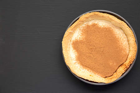 Homemade Sugar Cream Pie in a baking dish on a black background, top view. Overhead, from above, flat lay. Copy space.