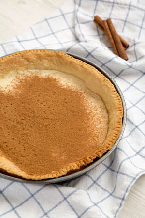 Homemade Sugar Cream Pie in a baking dish on a white wooden background, side view.