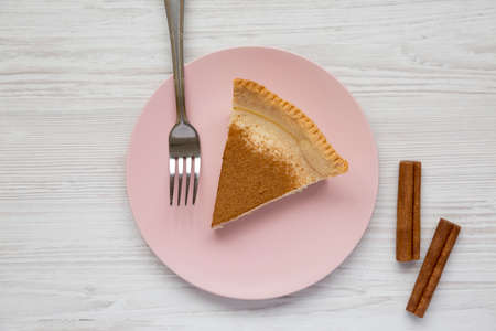 Homemade Sugar Cream Pie on a pink plate on a white wooden table, top view. Flat lay, overhead, from above. 写真素材