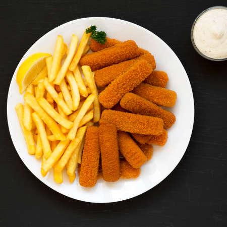 Homemade Fish Sticks and Fries with Tartar Sauce on black surface, top view. Flat lay, overhead, from above.