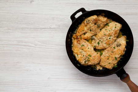 Homemade Italian Chicken Piccata in a cast iron pan, top view. Overhead, from above, flat lay. Copy space.