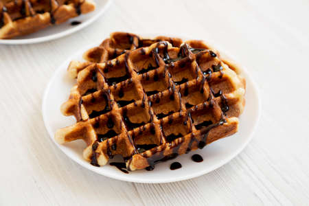 Yummy Homemade Belgian Sugar Waffles on a white plate on a white wooden background, low angle view.
