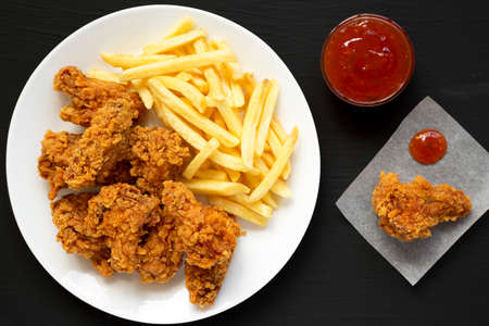 Homemade Crispy Chicken wings and French Fries with sour-sweet sauce on a black background, view from above. Top view, overhead, flat lay.