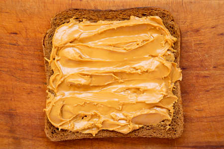 Piece of Bread with Peanut Butter on a rustic wooden board, top view. Close-up.