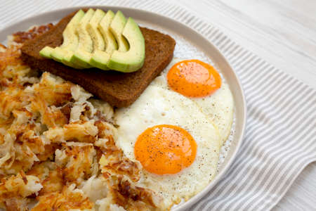 Tasty Homemade Fried Hashbrowns and Eggs on a plate, low angle view. Copy space.