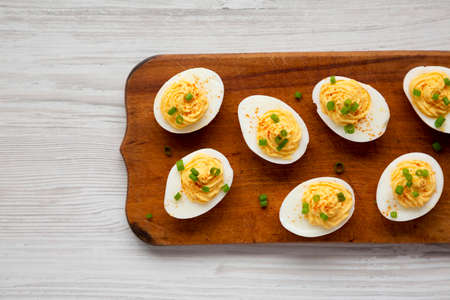 Homemade Deviled Eggs with Chives on a rustic wooden board, view from above. Flat lay, top view, overhead.