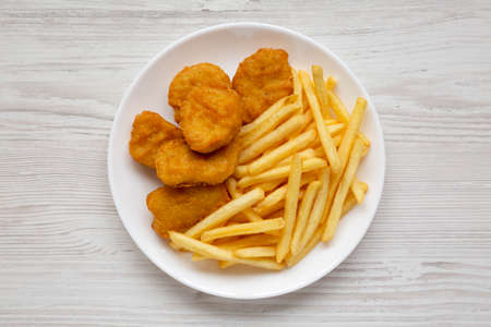Tasty Fastfood: Chicken Nuggets and French Fries on a plate on a white wooden background, top view. Overhead, from above, flat lay.