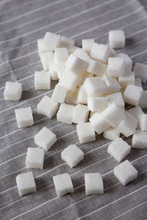 Organic White Sugar Cubes on cloth, side view. Close-up.
