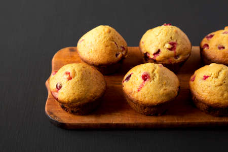 Homemade Cranberry Muffins with Orange Zest on a rustic wooden board on a black background, side view. Copy space.