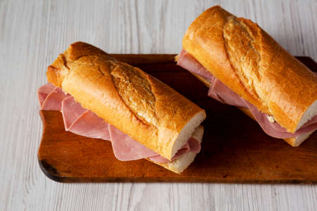 Homemade Parisian Jambon-Beurre Sandwich on a rustic wooden board on a white wooden table, low angle view.