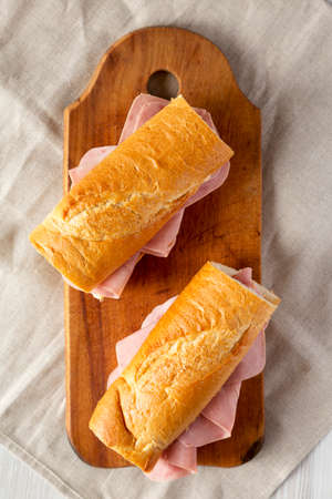 Homemade Parisian Jambon-Beurre Sandwich on a rustic wooden board, top view. Flat lay, overhead, from above. Stockfoto