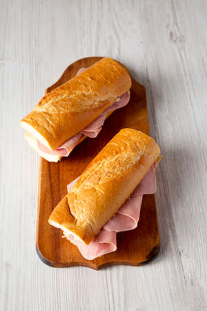 Homemade Parisian Jambon-Beurre Sandwich on a rustic wooden board on a white wooden background, low angle view.