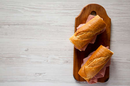 Homemade Parisian Jambon-Beurre Sandwich on a rustic wooden board on a white wooden surface, top view. Flat lay, overhead, from above. Copy space.